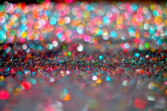 Abstract bright colored bokeh background. Lurex fabric. The small depth of field.