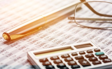 Calculator, pen, glasses and the financial report. Close up