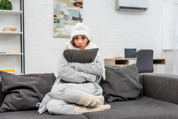 freezed young woman in warm clothes sitting on couch and hugging cushion at home