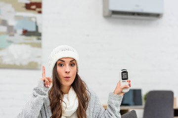 freezed young woman in warm clothes having idea while holding air conditioner remote control at home