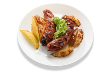 Fried sausages with a vegetable side dish and potatoes. Isolated on white