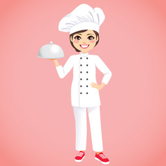 Young beautiful happy female chef wearing white uniform holding silver tray on pink background