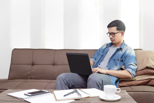 A freelance asian man sitting on sofa using laptop working from home