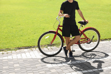 Man with bike outdoors on sunny day, space for text