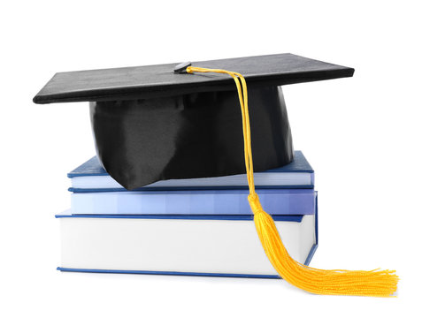 Graduation hat with gold tassel and stack of books isolated on white
