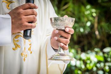 padre catolico celebrando misa con copa de vino