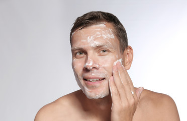 Man washing face with soap on white background