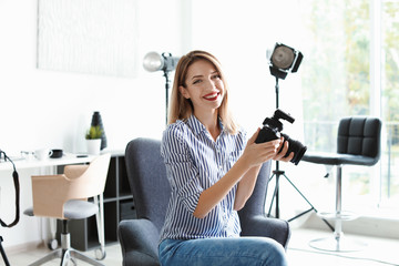 Portrait of female photo blogger with camera at home