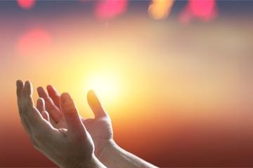 Hands of human praying on cross bokeh
