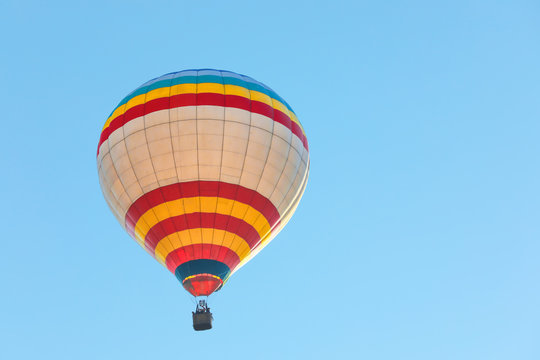 Colorful hot air balloon flying in blue sky. Space for text