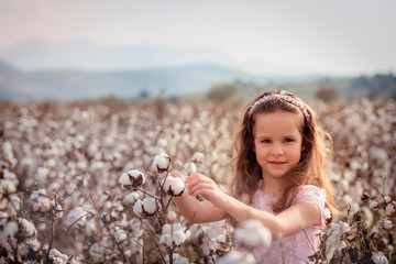 Beautiful little girl with long hair and in pink dress in cotton field