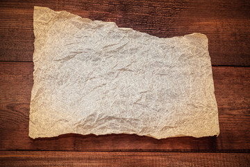 Sheet of parchment on a wooden background. Crumpled sheet of parchment paper as background, texture.
