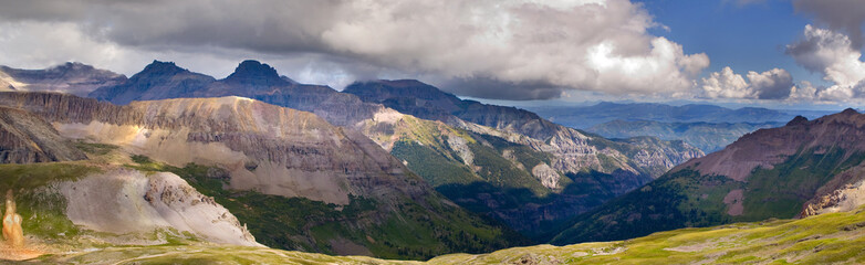 Imogene Pass Ouray Colorado with billowing clouds, high altitude vegetation, boulders broken by weathering, and layering of mountains  in the distance.