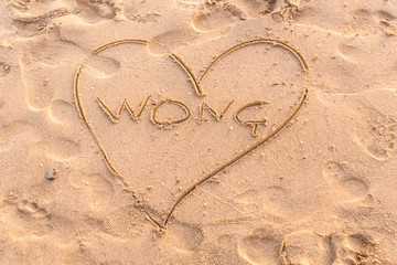 Summer drawn letters on a sandy beach. Text template pattern. Creative typography for holiday greetings.
