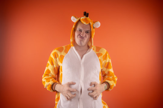 pajamas in the form of a giraffe. emotional portrait of a guy on an orange background. crazy and funny man in a suit. animator for children's parties