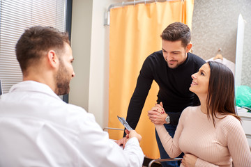 A handsome male doctor shows ultrasound picture to the young pregnant couple.