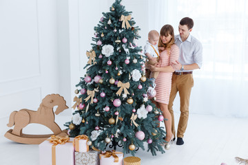 Mom and Dad hold their son in their arms near the Christmas tree