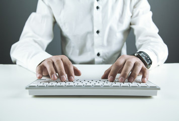 Businessman typing on a computer keyboard . Business concept