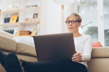 Serious blond woman surfing the internet