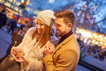A beautiful young couple smiling and checking the gifts in a christmas market.