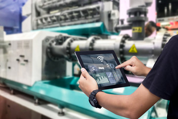Smart industry control concept.Hands holding tablet on blurred automation machine as background Fotoväggar