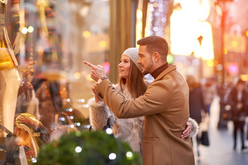 A beautiful young couple walking on the street and checking the storefront with christmas decoration.