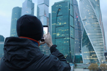 A man photographs the skyscrapers on the phone