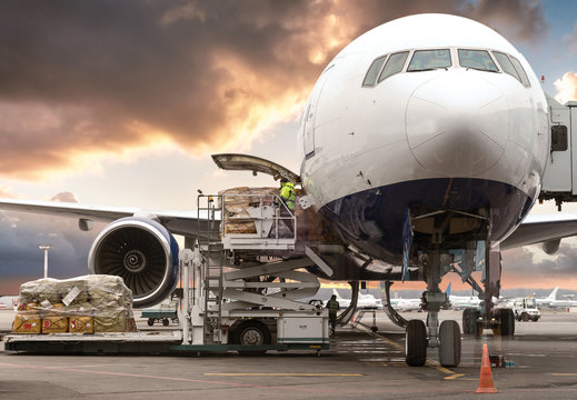 loading cargo into the aircraft before departure with nice sky