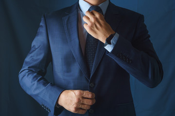 A man in a blue suit straightens his tie
