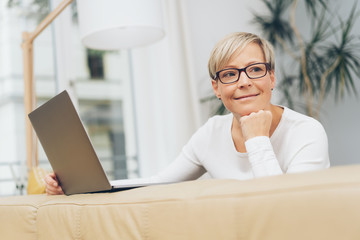 Smiling mature woman relaxing with her laptop