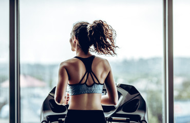 Attractive woman running on treadmill in sport gym, sport life and sport equipment. Back view.