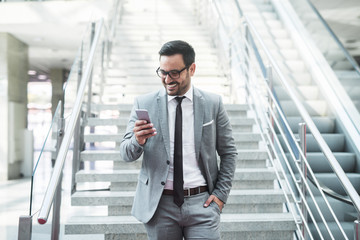 Young successful businessman going down the staircase and using smart phone for text message.