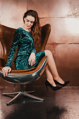 Attractive young woman in a blue green velvet dress, sitting in a leather brown chair, looking down. Long hair, legs, high heels. Luxury concept