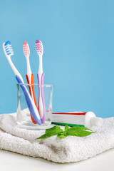 Healthy teeth. Toothbrush in a glass and toothpaste and mint leaves a bath towel on the table in the bathroom on a blue background. Design, health care, hygiene health and fresh breath
