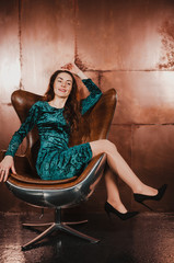 Attractive young woman in a blue green velvet dress, sitting in a leather brown chair, having fun. Long hair, legs, high heels. Luxury concept