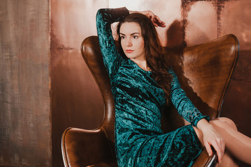 Attractive young woman in a blue green velvet dress, sitting in a leather brown chair, having fun. Long hair, legs. Luxury concept. Copy space for your text and design