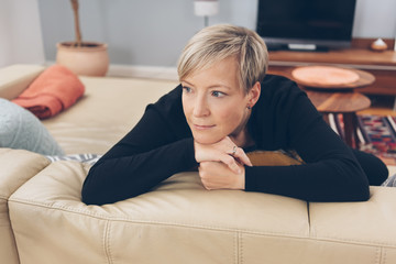 Woman sitting daydreaming at home