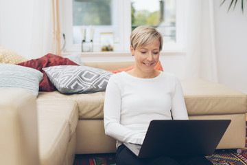Blond woman smiling as she works on her laptop