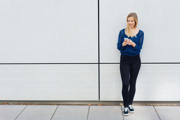 Blond woman using a mobile on an urban sidewalk
