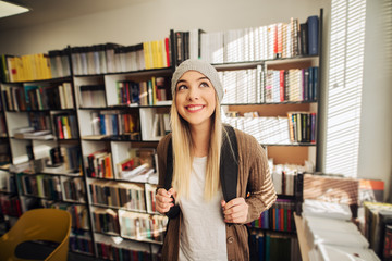 Cute happy school girl standing in library with backpack on her back. Smiling and looking away and satisfied.