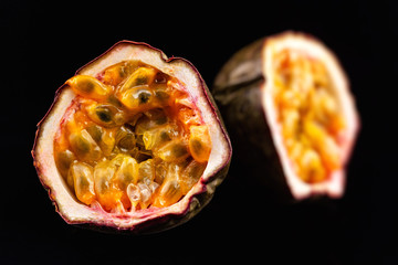 Macro image of two halves of passion fruit isolated at black background.