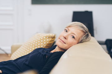 Blond woman relaxing on a couch at home