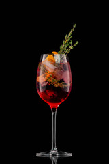Glass of red sangria wine cocktail decorated with thyme and orange isolated at black background.