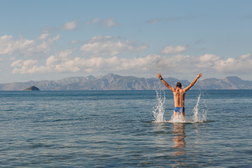 A young man jumping in the sea against the backdrop of mountains with hands up