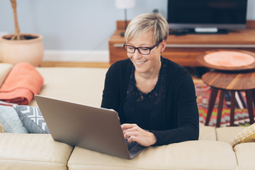 Happy smiling woman using a laptop at home