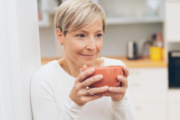 Woman enjoying a large cup of coffee or soup