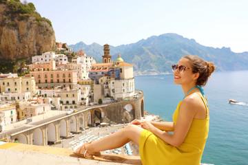 Beautiful young woman sitting on wall with panoramic view of Atrani village on Amalfi Coast, Italy Wall mural