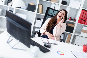 A young girl sitting at an old computer, talking on the phone and laughing.