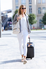 Beautiful young business woman walking with suitcase in the street.