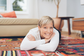 Woman relaxing on a colorful floor rug at home